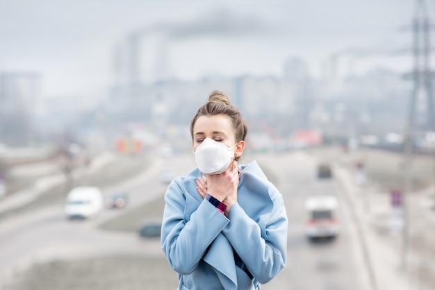 Giovane donna in maschera protettiva che si sente male in città con l'inquinamento atmosferico dovuto al traffico e alla produzione. concetto di smog