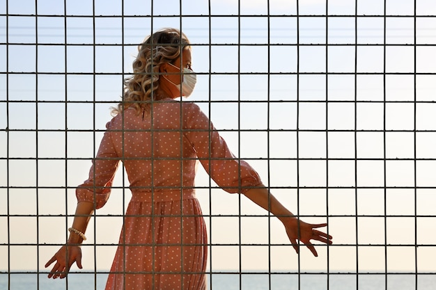 Giovane donna in maschera protettiva sta con la schiena al reticolo e guarda la luce