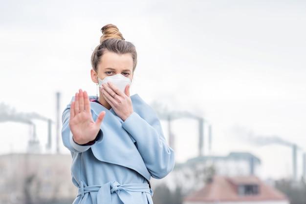 Giovane donna in maschera protettiva che soffre di inquinamento atmosferico dovuto alla grande produzione in città