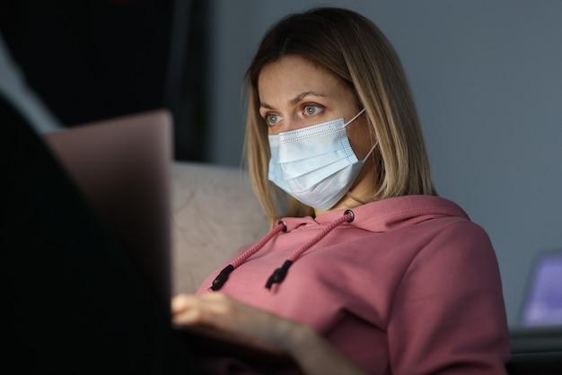 Giovane donna nella mascherina medica protettiva che si siede davanti al computer portatile a casa