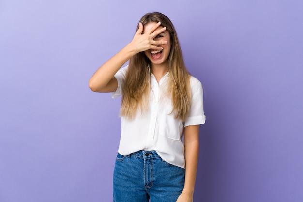 Giovane donna sopra il muro viola che copre gli occhi a mano e sorridendo