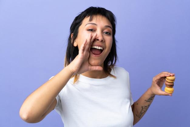 Giovane donna sopra la parete viola che tiene macarons e gridare francesi variopinti