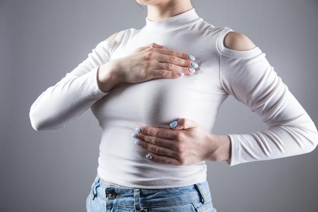 Una giovane donna si è messa una mano sul petto in una scena grigia