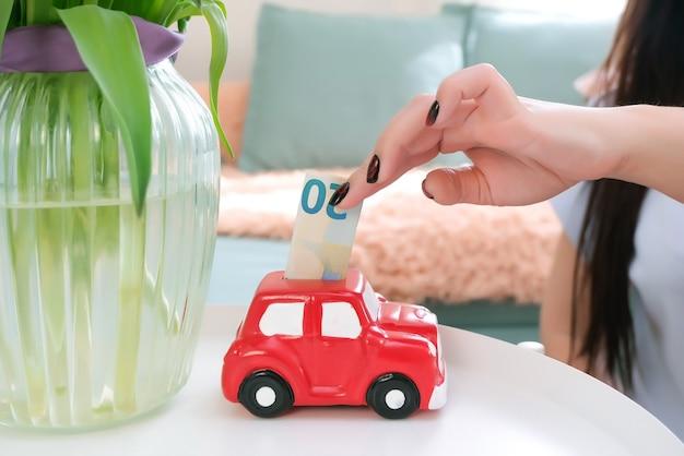 La giovane donna mette i soldi in un salvadanaio, risparmiando per un'auto.