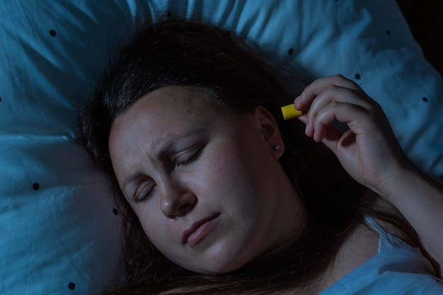 Giovane donna che mette i tappi per le orecchie nelle orecchie per la riduzione del rumore prima di dormire, insonnia