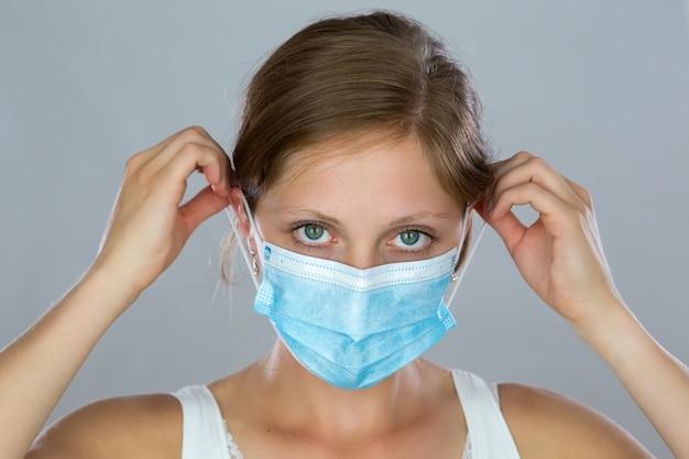 Giovane donna che indossa la maschera per il viso durante la pandemia.