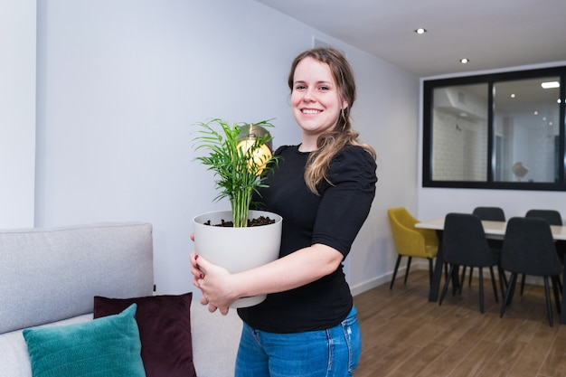 Giovane donna che mette piante nella sua nuova casa