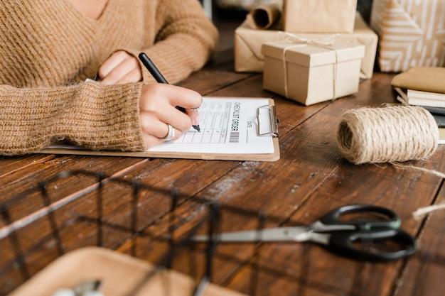Giovane donna che mette le zecche da merci ordinate nella lista di controllo mentre è seduto da un tavolo di legno tra scatole imballate