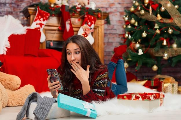 Giovane donna in quarantena che parla di videochiamate sullo sfondo delle decorazioni natalizie