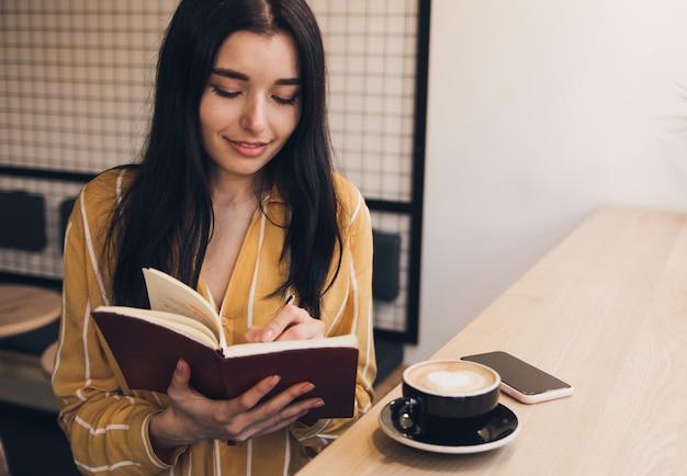 La giovane donna ha letto il libro e beve il caffè in caffè