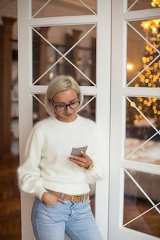 La giovane donna legge i messaggi di auguri per il nuovo anno nei social media messenger con un sorriso compiaciuto. le donne festeggiano il natale a casa da sole e leggono gli sms di familiari e amici. concetto di vacanze invernali