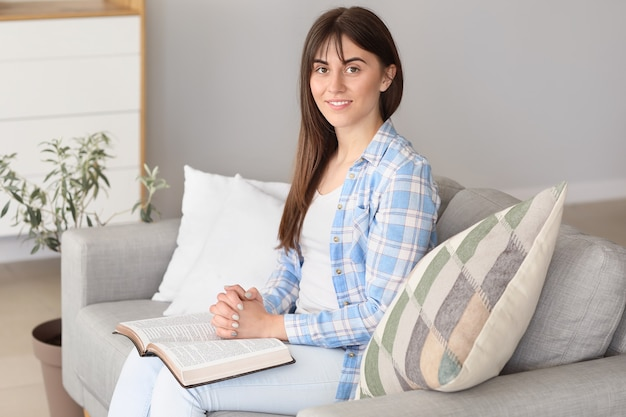 Giovane donna che legge la bibbia a casa