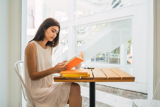 Giovane donna che legge un libro alla caffetteria.