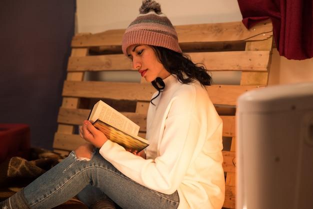 Giovane donna che legge un libro in un'atmosfera confortevole e rilassata con un pallet dietro
