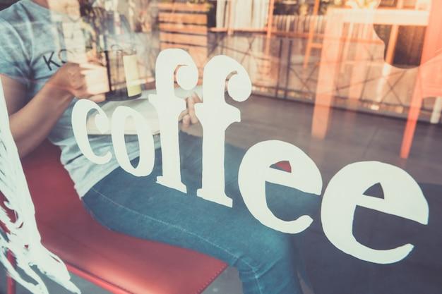 Giovane donna che legge un libro e che tiene tazza di caffè