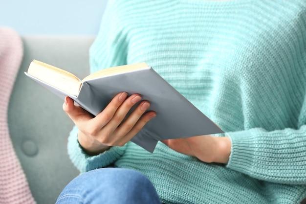 Libro di lettura della giovane donna a casa, primo piano