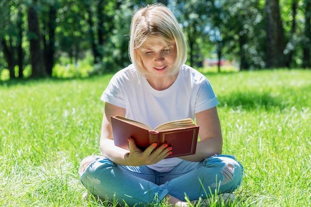 Giovane donna che legge un libro in un parco un giorno di estate soleggiato. bionda in maglietta e jeans bianchi. tempo libero e hobby.