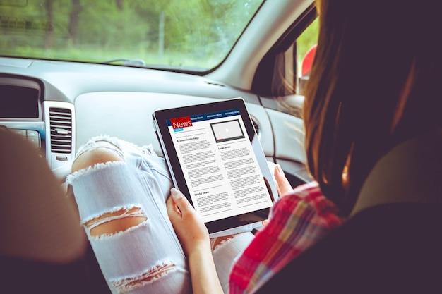 Giovane donna che legge le notizie utilizzando tablet mentre era seduto in carv