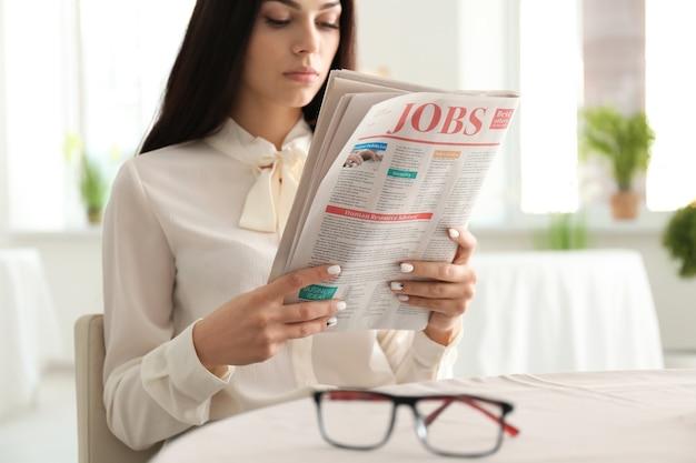 Giovane donna che legge il giornale nella caffetteria