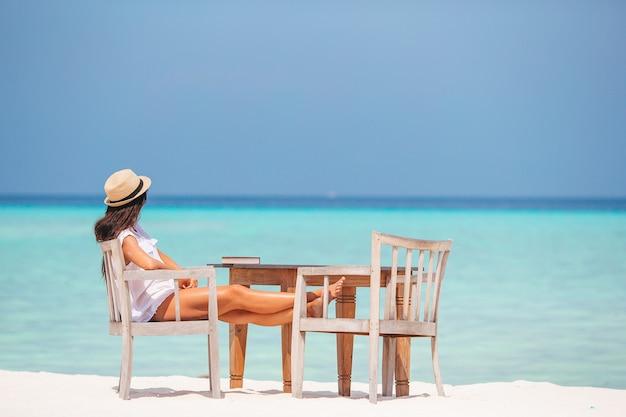 Giovane donna che legge al caffè all'aperto della spiaggia