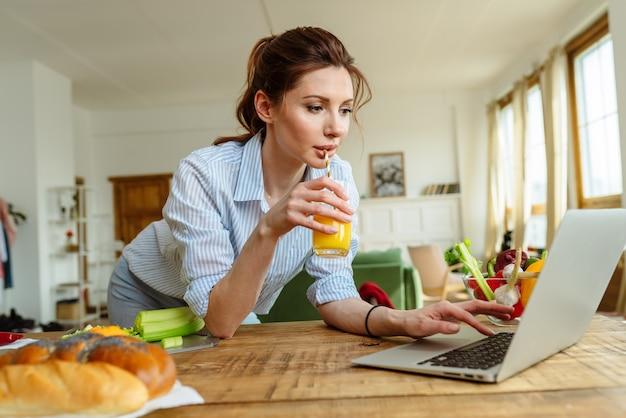 Una giovane donna legge una ricetta online sul suo laptop cucinando il pranzo con verdure fresche