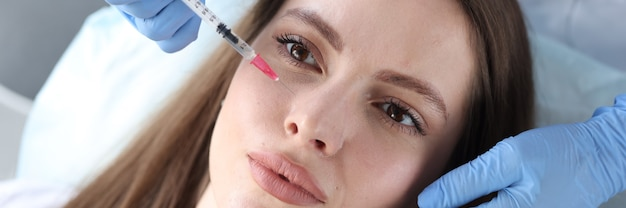 Giovane donna che riceve un'iniezione antietà nella clinica di bellezza