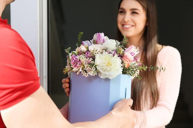Giovane donna che riceve bellissimi fiori dal fattorino a casa