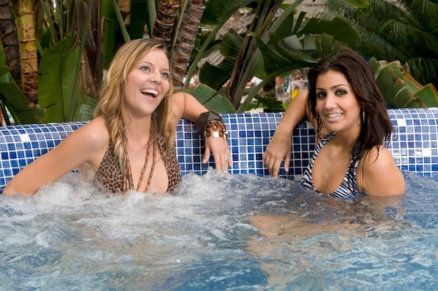 Giovane donna che riceve un trattamento per il corpo in un luogo di massaggio con un bagno di bolle nell'acqua