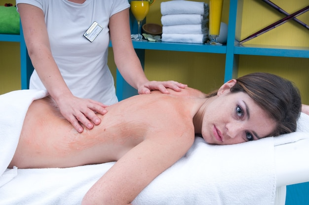 Giovane donna che riceve un trattamento per il corpo in un luogo di massaggio