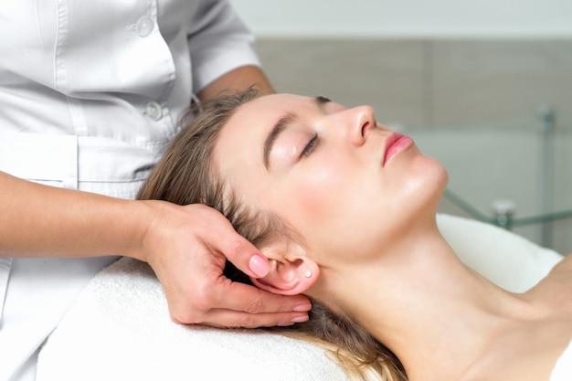 Giovane donna che riceve un massaggio alla testa dall'estetista femmina.