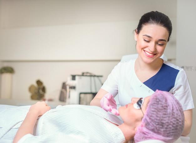 Giovane donna che riceve un trattamento laser in cosmetologia clinica. occhi coperti con occhiali protettivi