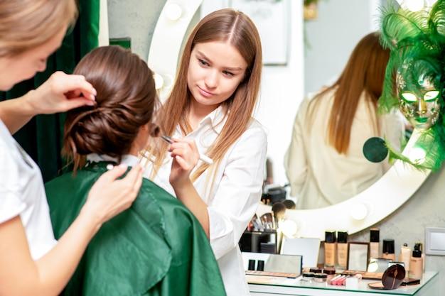 Giovane donna che riceve trucco e acconciatura da truccatore professionista e parrucchiere nel salone di bellezza.