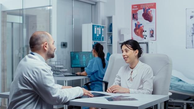 Giovane donna che riceve una buona notizia dal medico dopo aver consultato i raggi x, sorride ed è felice.