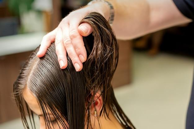 Giovane donna che riceve il trattamento i suoi capelli dalle mani del parrucchiere professionista nel parrucchiere