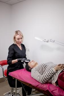 Giovane donna che riceve ultrasuoni cavitazione peeling facciale pulizia cosmetologia cura della pelle del viso tr...