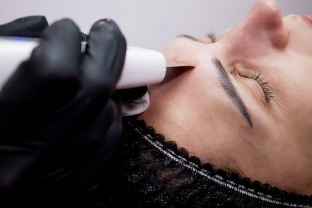 Giovane donna che riceve la pulizia del peeling facciale con cavitazione ad ultrasuoni. cosmetologia pulizia del trattamento per la cura della pelle del viso.