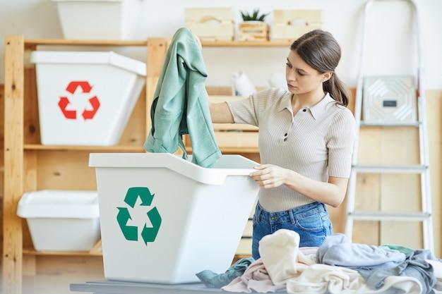 Giovane donna che ricicla il suo guardaroba getta i suoi vestiti nel cestino