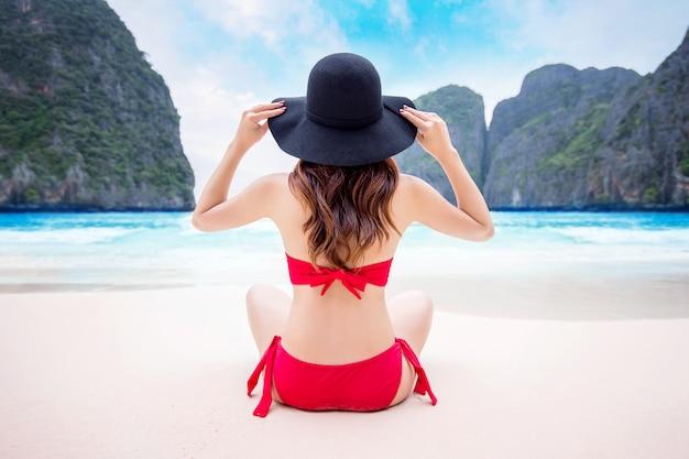 Giovane donna in bikini rosso che si siede sulla spiaggia.