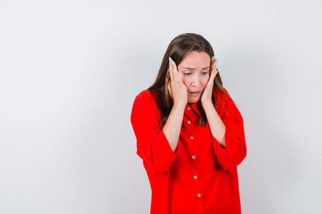 Giovane donna in camicetta rossa che tiene le guance con le palme e sembra sconvolta, vista frontale.