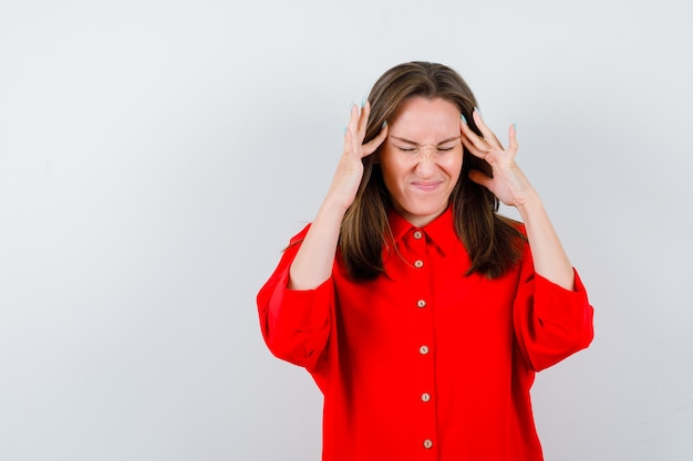 Giovane donna in camicetta rossa con le dita sulle tempie e guardando scontento, vista frontale.