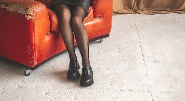 Giovane donna su una sedia rossa. elegante donna in abito nero e collant seduto su una vecchia sedia retrò. foto di concetto di bellezza e glamour