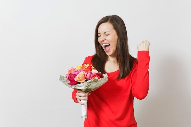 Giovane donna in vestiti rossi che tengono il mazzo di bei fiori delle rose, facendo il gesto del vincitore isolato su fondo bianco. san valentino o giornata internazionale della donna, compleanno, concetto di vacanza.