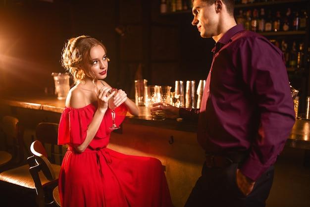 Giovane donna in abito rosso flirta con l'uomo dietro il bancone del bar. data in discoteca, coppia di innamorati attraente al pub