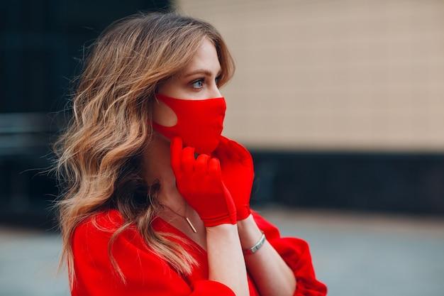 La giovane donna in vestito e guanti rossi mette sulla mascherina medica