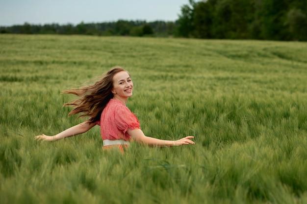 Giovane donna in vestito rosso e cappello che cammina nel campo verde dell'orzo in campagna