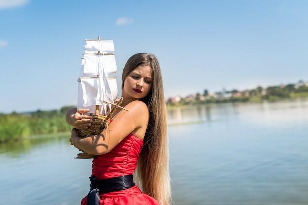 Giovane donna in abito rosso con modello di nave in riva al mare