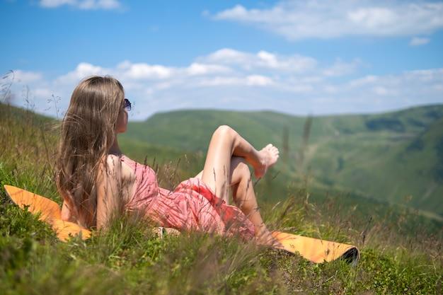 Giovane donna in abito rosso sdraiato sul prato erboso verde in una calda giornata di sole in montagne estive godendo della vista della natura.
