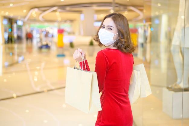 Una giovane donna in abito rosso che indossa una maschera protettiva nel centro commerciale, che fa shopping secondo il concetto di pandemia di covid-19.