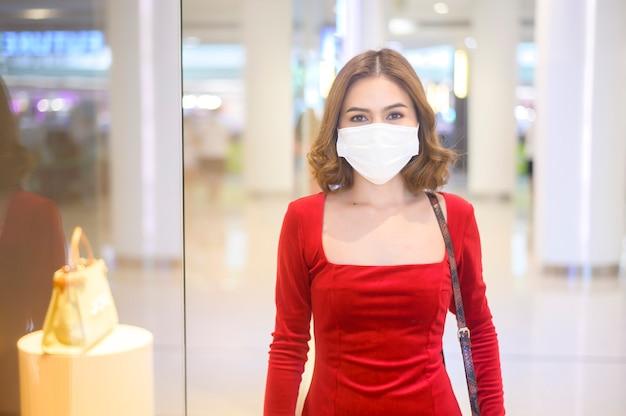 Una giovane donna in abito rosso che indossa una maschera protettiva nel centro commerciale