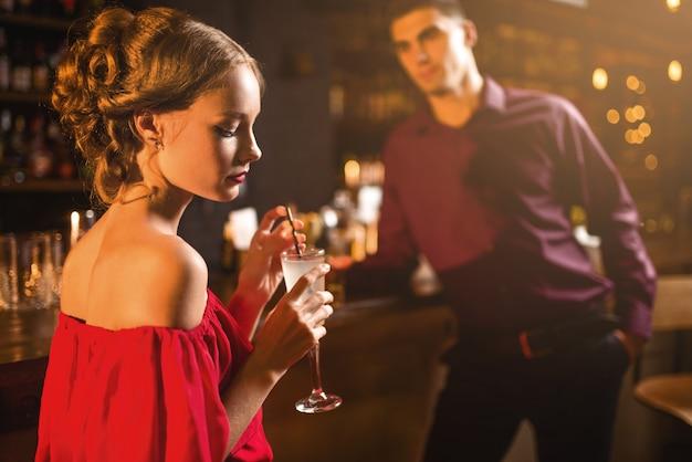 Giovane donna in abito rosso con cocktail in mano, uomo dietro il bancone del bar, flirtare. data in discoteca, coppia di innamorati attraente al pub